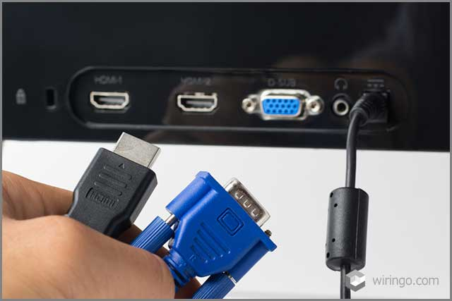 HDMI and VGA cables against a monitor with ports