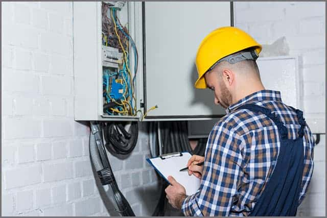 Professional electrician inspecting wires in the electrical box