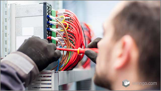 electrician engineer works with electric cable wires of the fuse switch box