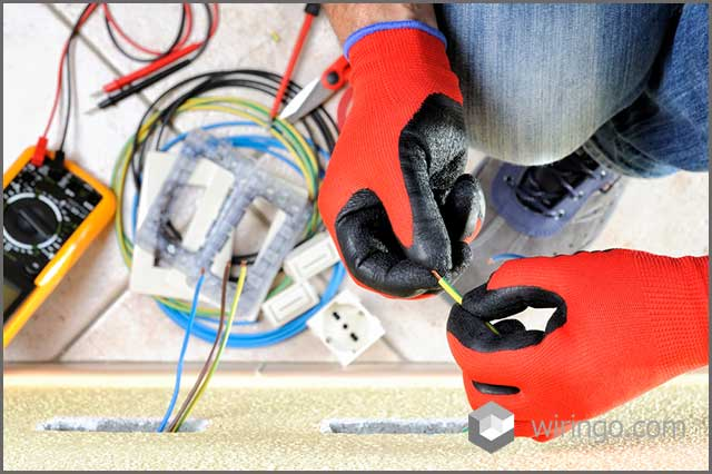 Electrician technician at work prepares the cable