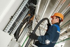 Electrician builder engineer installing industrial cable