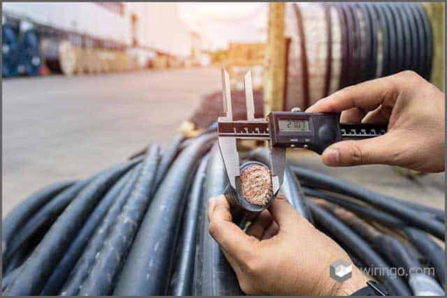 The technician manually measures the diameter of the power cord