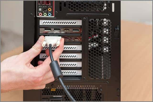 A Man Connecting A DVI Cable with A D-sub Connector to A Monitor
