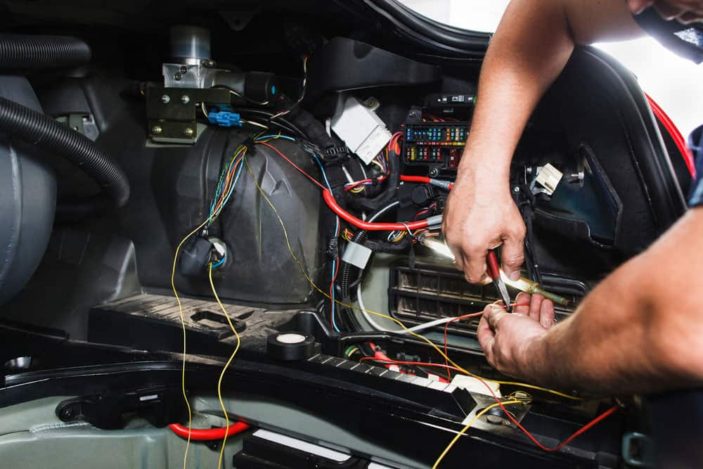 An electrician works with the car's electrical system