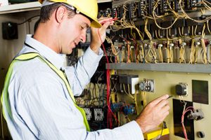 An electrician checking an industrial machine